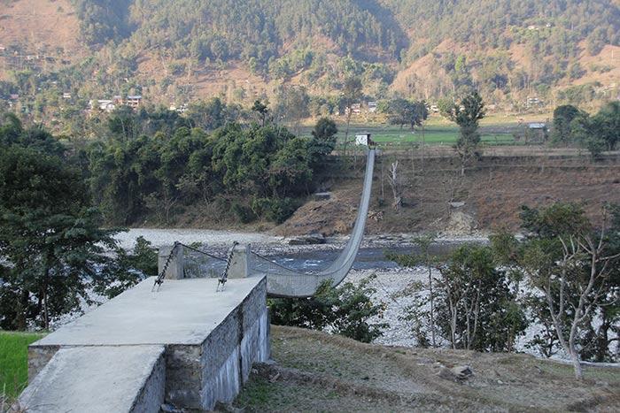 Great Himalayan trail- crossing suspension bridge in the Mountain